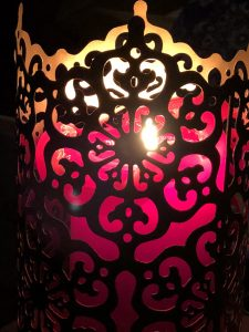 lit red candle in a tall brass holder with cutouts, all on a dark background